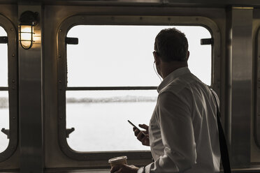 Businessman on a ferry looking out of window - UU09345