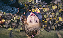 Portrait of laughing little girl standing in the woods, top view - DAPF00470
