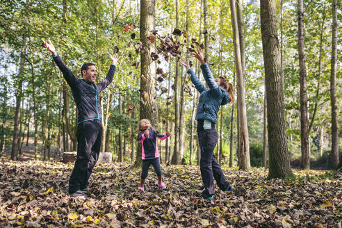 Happy family throwing autumn leaves in the air - DAPF00479