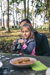 Little girl with binocular relaxing with her father in a forest - DAPF00494