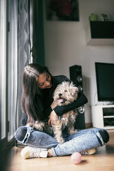 Happy young woman with her dog at home - JASF01299