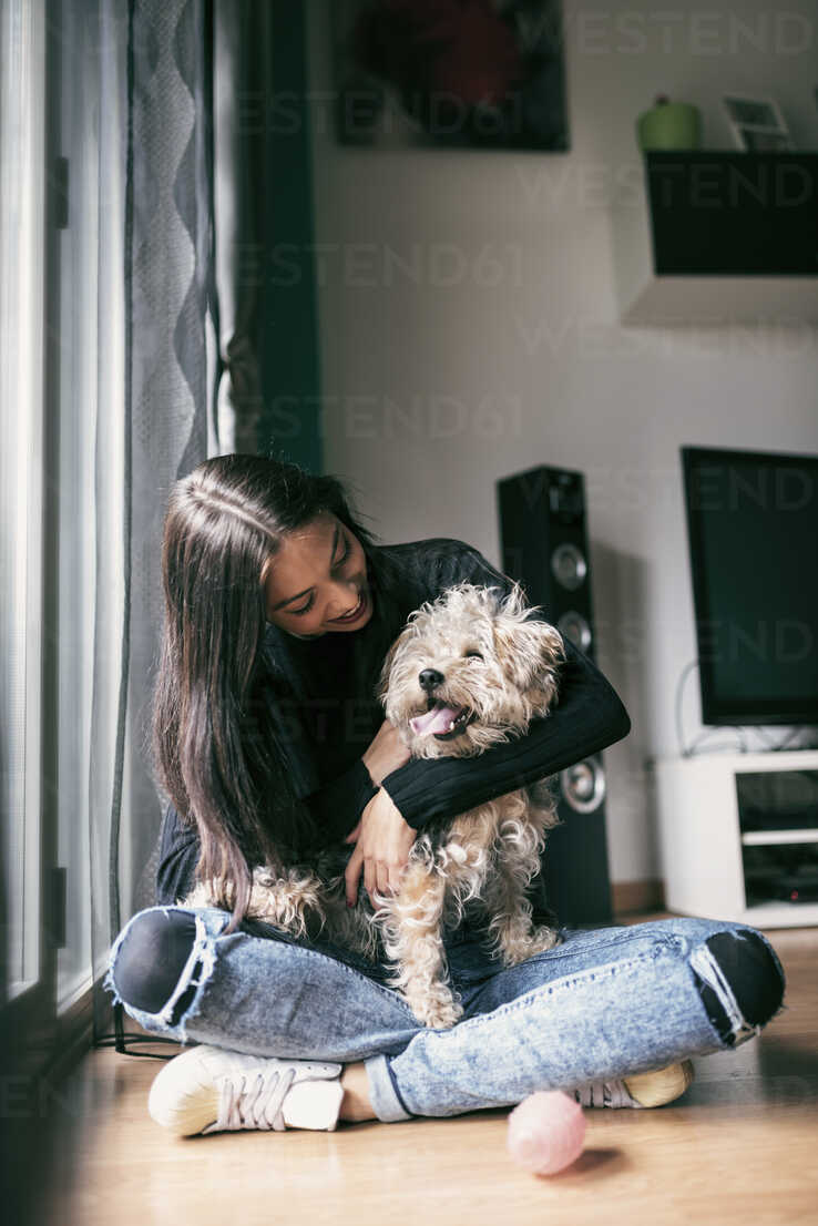 Happy young woman with her dog at home - JASF01299 - Jaen Stock/Westend61