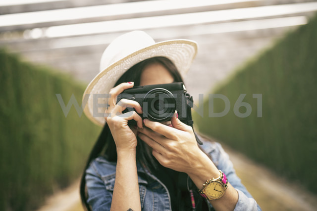 Young woman wearing hat taking picture of viewer - JASF01305