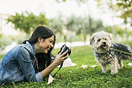 Laughing young woman lying on meadow taking picture of her dog - JASF01311