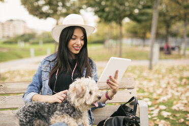 Young woman sitting on bench in a park with her dog looking at tablet - JASF01314