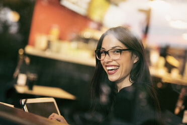 Portrait of laughing young woman sitting behind windowpane of a coffee shop with tablet - JASF01320