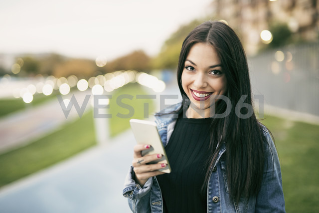 Portrait of smiling young woman with smartphone - JASF01323