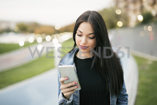 Portrait of young woman looking at smartphone - JASF01326 - Jaen Stock/Westend61