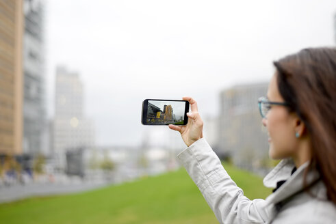 Germany, Berlin, woman taking picture with cell phone at Potsdamer Platz - BFRF01791