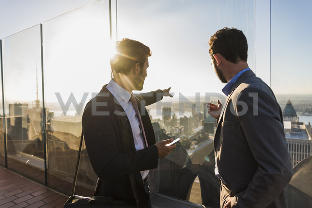 USA, New York City, two businessmen on Rockefeller Center observation deck - UU09356