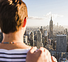 USA, New York City, woman looking on cityscape on Rockefeller Center observation deck - UU09371