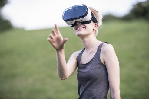 Smiling young woman using Virtual Reality Glasses outdoors - TAMF00833