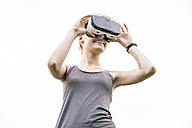 Smiling young woman using Virtual Reality Glasses outdoors - TAMF00836