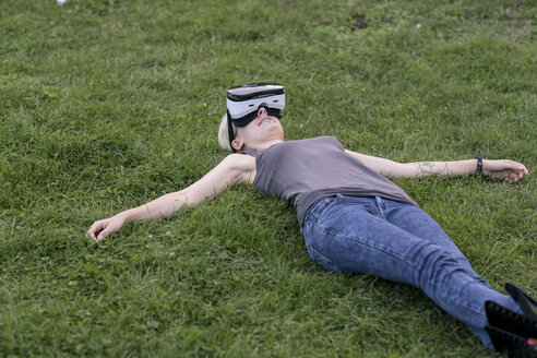 Young woman lying on a meadow wearing Virtual Reality Glasses outdoors - TAMF00839