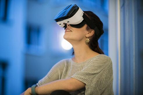 Young woman sitting beside window wearing Virtual Reality Glasses - TAMF00845