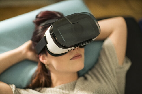Young woman using Virtual Reality Glasses at home - TAMF00848