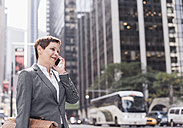USA, New York City, businesswoman in Manhattan talking on cell phone - UUF09391