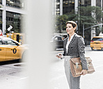 USA, New York City, businesswoman in Manhattan with cell phone - UUF09394