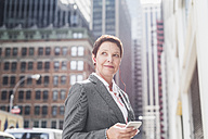 USA, New York City, businesswoman in Manhattan with with cell phone and earphones - UUF09403