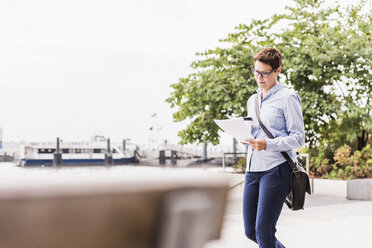 USA, New York City, businesswoman walking at East River reading document - UUF09412