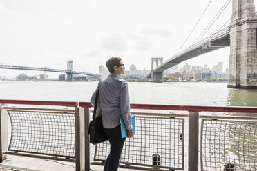 USA, New York City, woman standing at East River - UUF09418