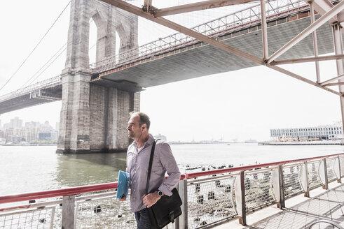 USA, New York City, man walking at East River - UUF09421