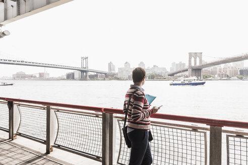 USA, New York City, woman at East River - UUF09427