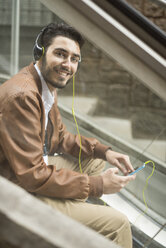 Smiling man with cell phone and headphones sitting on escalator - JASF01333