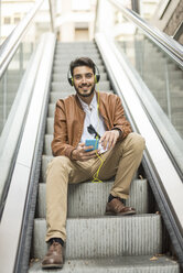 Smiling man with cell phone and headphones sitting on escalator - JASF01336