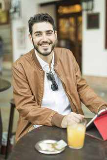 Smiling man with tablet and juice at outdoor cafe - JASF01339