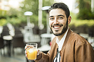 Smiling man drinking juice at outdoor cafe - JASF01342