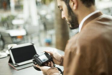 Young man looking at camera at outdoor cafe - JASF01345