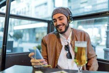 Smiling man with headphones and cell phone at outdoor bar - JASF01348
