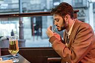 Young man smoking a cigarillo at outdoor bar - JASF01351