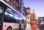 Man with slooking at cell phone at night in the city - JASF01354