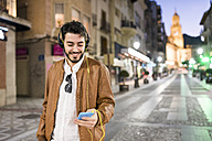 Smiling man with headphones and cell phone at night in the city - JASF01357