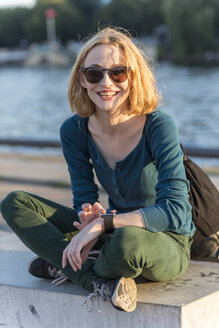 Portrait of smiling young woman wearing sunglasses and smartwatch - TAMF00863