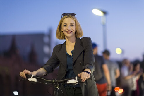 Germany, Berlin, portrait of smiling young woman with bicycle in the evening - TAMF00884