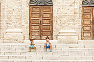 Two little boys sitting on stairs of an old building - VABF00846