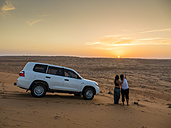 Oman, Al Raka, two young women standing besides off-road vehicle on a desert dune watching sunset - AMF05096