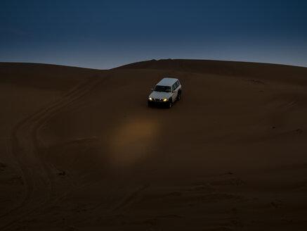 Oman, Al Raka, off-road vehicle parking on dune in Rimal Al Wahiba desert at twilight - AMF05105