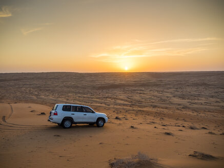 Oman, Al Raka, off-road vehicle parking on dune in Rimal Al Wahiba desert at sunset - AMF05111