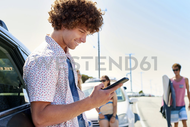 Smiling young man at a car checking his cell phone - WESTF21979 - Fotoagentur WESTEND61/Westend61