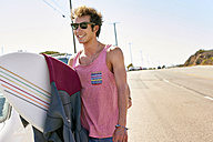 Smiling young man carrying surfboard on coastal road - WESTF21982