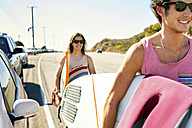 Smiling young couple carrying surfboards on coastal road - WESTF21988