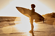 Young man holding surfboard on the beach at sunset - WESTF21991
