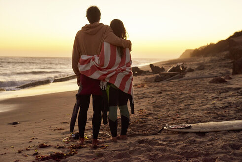 Couple embracing on the beach at sunset next to surfboard - WESTF21997