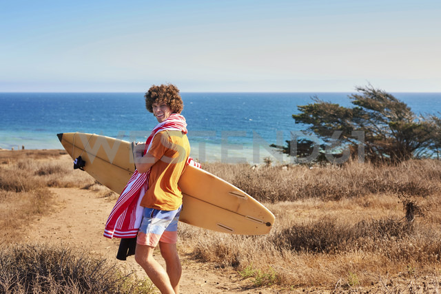 Young man carrying surfboard at the coast - WESTF22006
