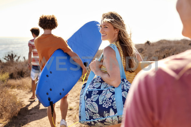 Friends carrying surfboards at the coast - WESTF22012 - Fotoagentur WESTEND61/Westend61