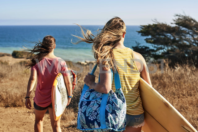 Two women carrying surfboards at the coast - WESTF22015 - Fotoagentur WESTEND61/Westend61
